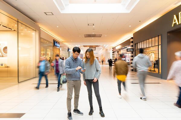 A man and a woman stand in a crowd in a shopping mall looking at a cell phone