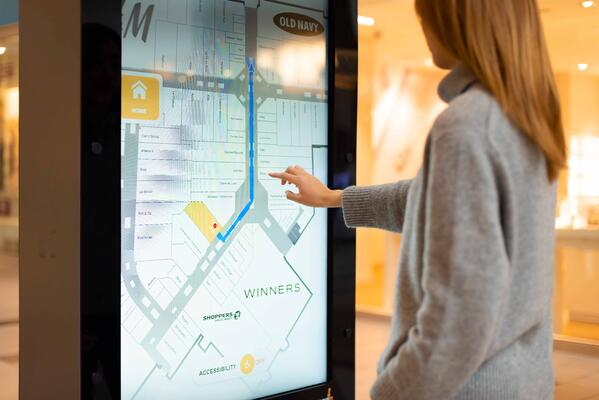 women selecting a store on a touchscreen display in a mall