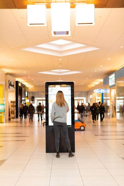 Woman at a digital directory in a mall