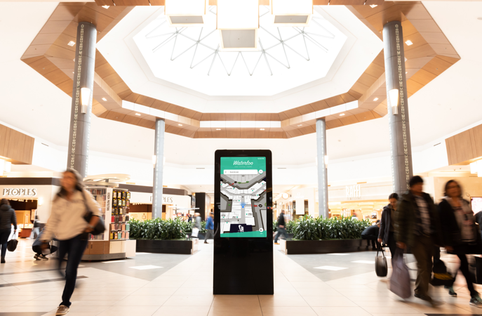 A kiosk inside a mall with people walking around