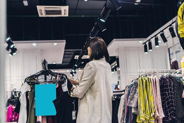 Woman standing in a store looking at clothing